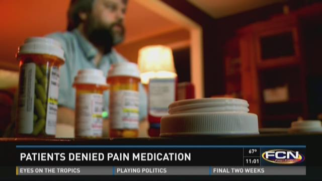 A pharmacist counts pain medication at a South Portland